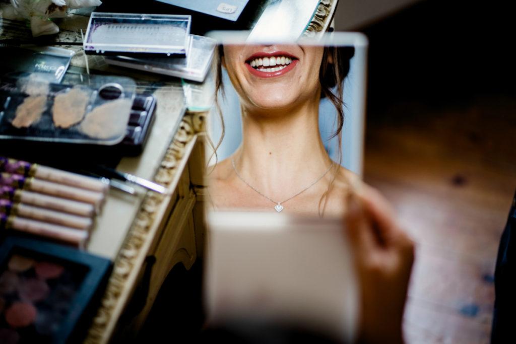 sonrisa de la novia reflejada en un espejo